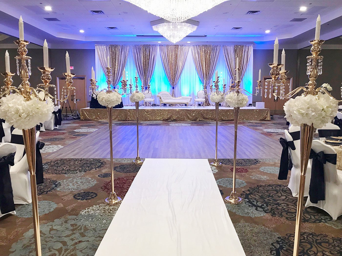 wedding reception set up with dance floor, lights, and flowers wide shot