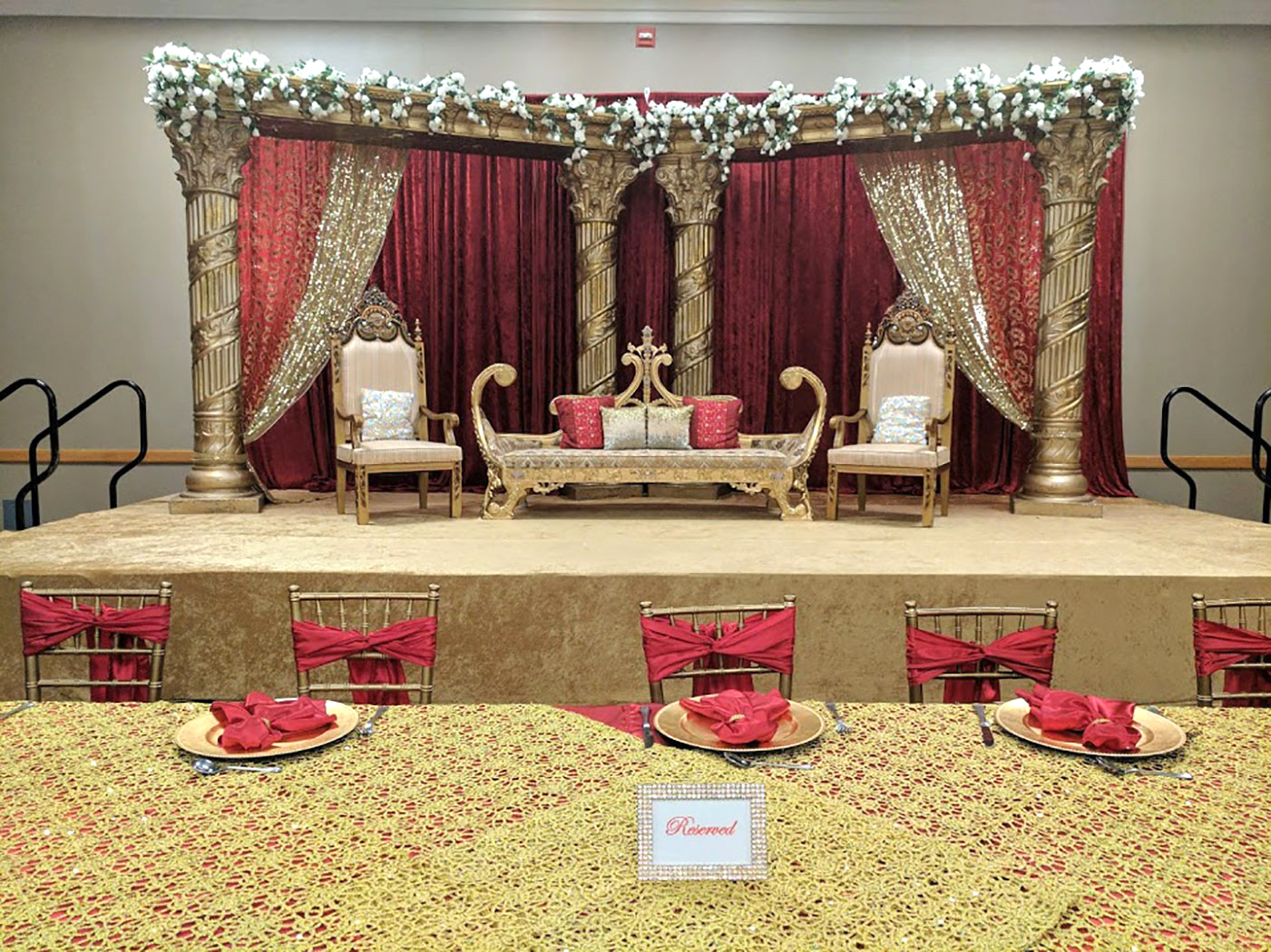 Ethnic wedding setup with red curtains and red pillows
