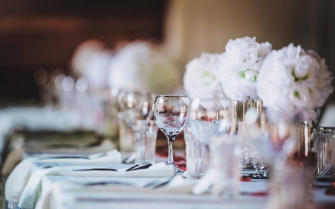 white table cloth with white flower arrangements and empty wine glasses