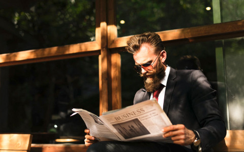 Man in suit reading newspaper outside