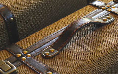 Close up of brown leather handle attached to wicker suitcase