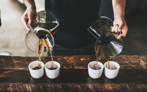 Barrista pouring coffee into four mugs