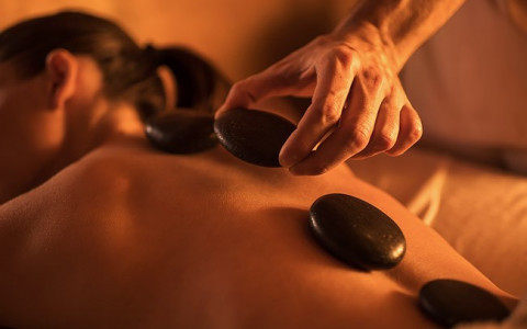 woman laying on a massage table with massage stones on her back