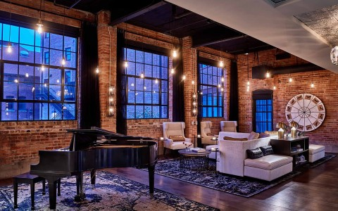 lobby area with piano and brick walls