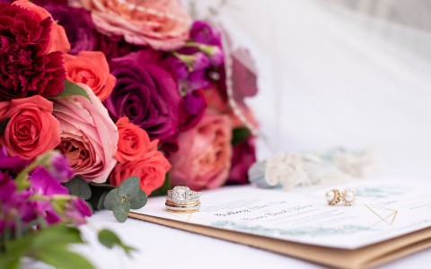 close up of a bridal bouquet, wedding rings and invitation