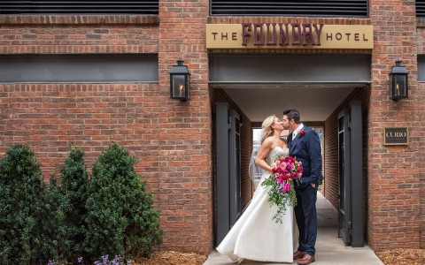 couple kissing on their wedding day in front of The Foundry Hotel