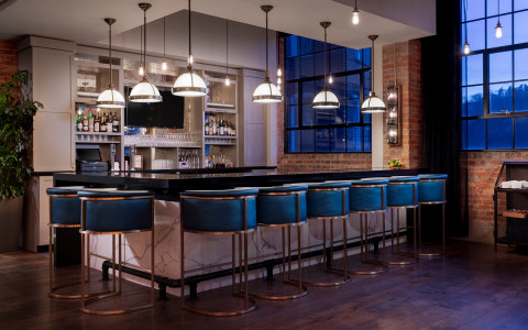 hotel bar with long ceiling lamps and blue stools