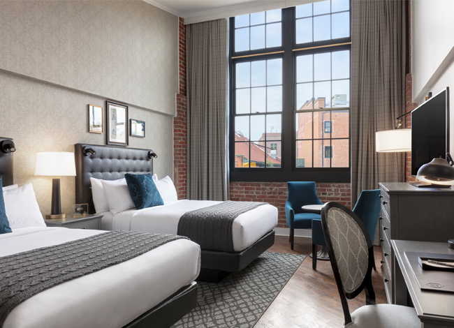 foundry double queen room with upholstered headboards and large windows