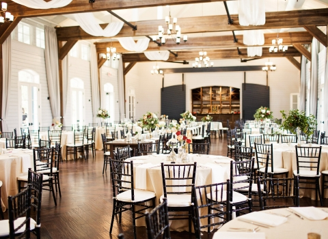 Stable event space set for wedding reception with round tables, wooden ceilings & rustic chandeliers
