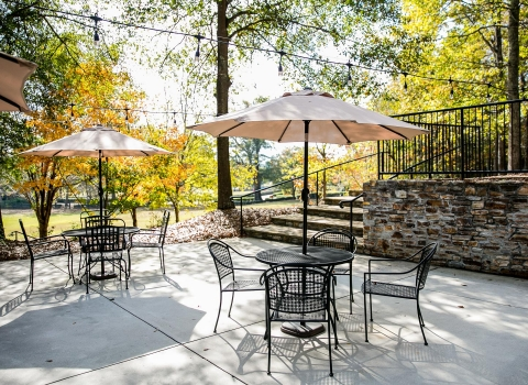 Outdoor terrace seating with metal tables and chairs with umbrellas