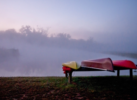 Kayaks set on wooden plank with fog in the back