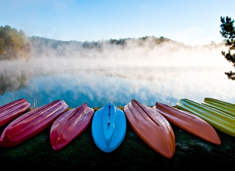 Row of colorful kayaks by river shore