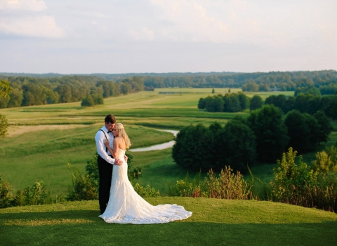 Wedding hugging & standing on vast green field with trees in the distance