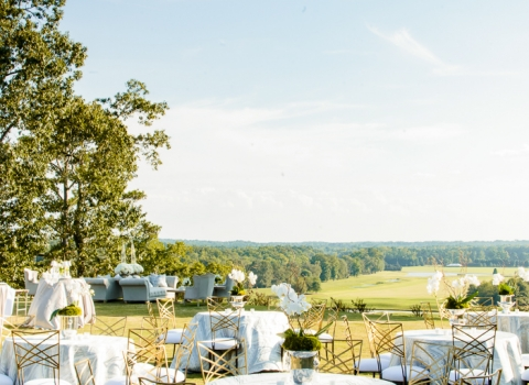 Outdoor wedding reception set up with round tables & white decor