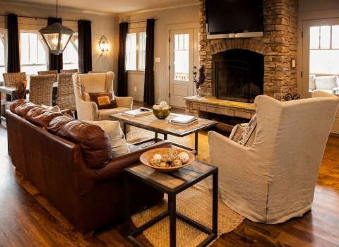 Lodge living space with brown leather couch, beige sofa chairs, wooden coffee table & brick fireplace