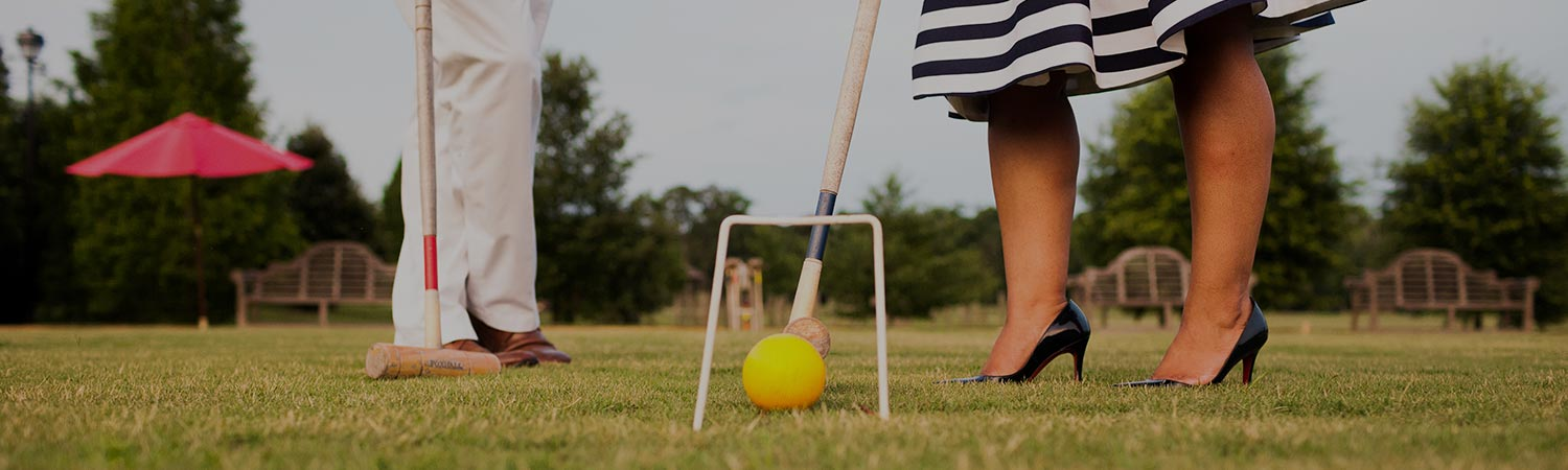 Close up of woman with heels on playing croquet next to man