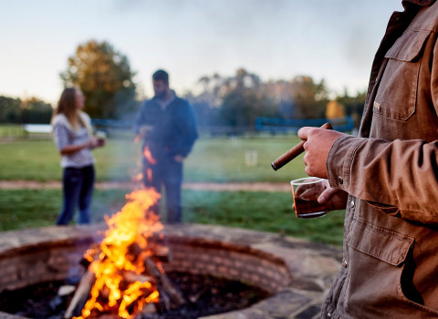 man smoking cigar and drinking in front of bonfire
