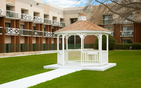 Gazebo in the middle of a field surrounded by hotel balconies