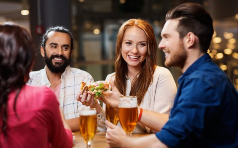 Cheerful group of friends eating and drinking beer