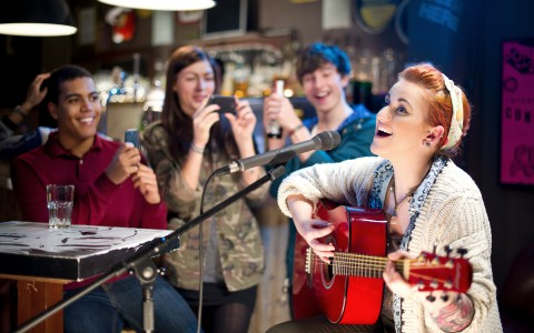 Woman singing and playing guitar while others smile and take pictures