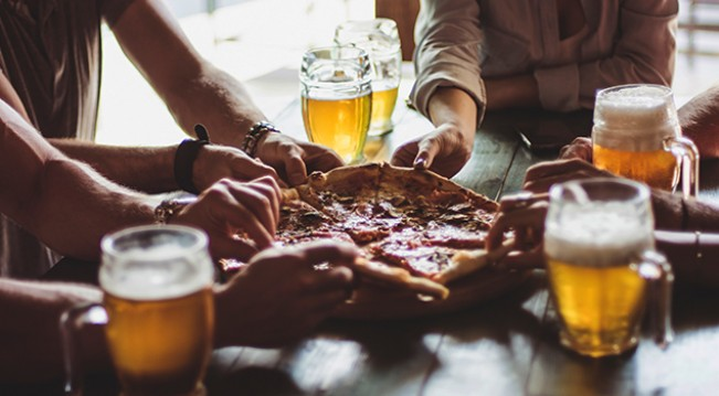 Group of friends splitting pizza and beer