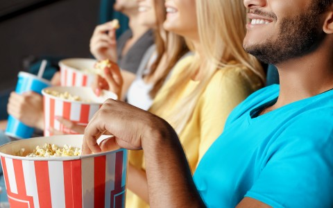 Cheerful people eating popcorn watching a movie