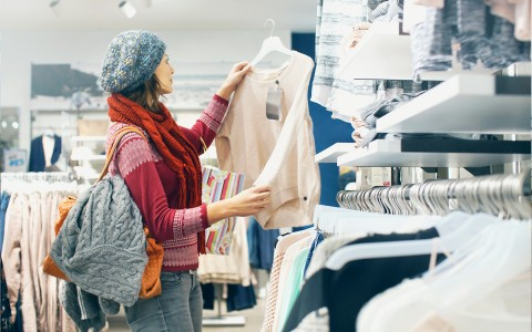 Woman wearing winter clothing shopping for a sweater