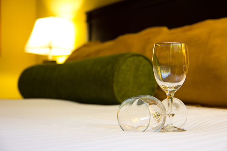 two wine glasses on a hotel bed