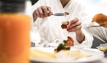 person eating breakfast room service in a robe