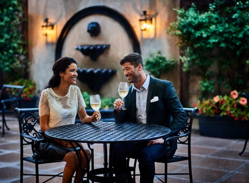Man and woman drinking white wine on the patio with a water fountain and garden behind them
