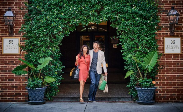 Couple walking out of the French Quarter Inn with shopping bags