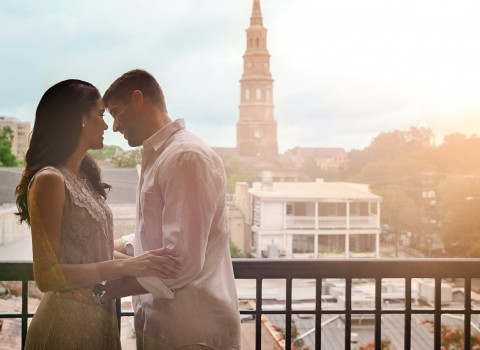 Couple looking into each others eyes and smiling out on the balcony with the town of St. Augustine in the background