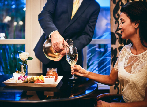 Man pouring wine into woman's glass, olive and nut tray on the table