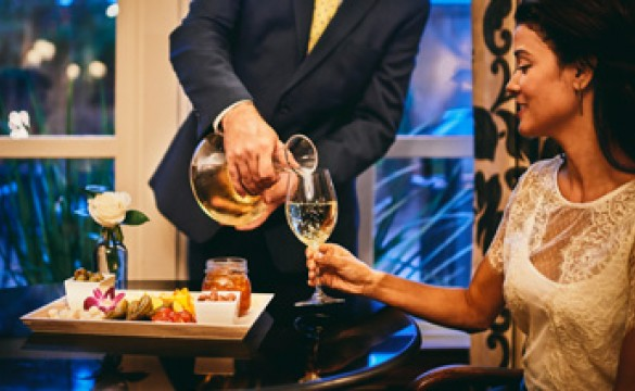 man pouring wine into a woman's glass at dinner