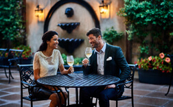 couple drinking wine at a table in a courtyard