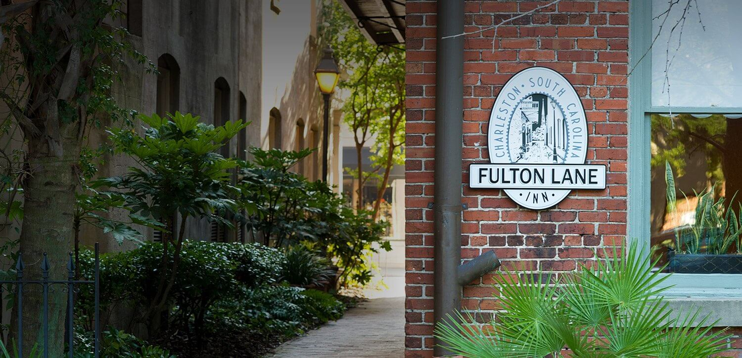 Corner of brick building with Fulton Lane logo sign