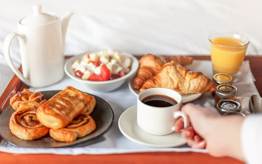 woman holding coffee cup on a tray of breakfast foods