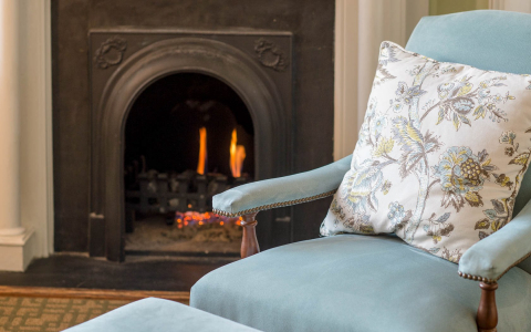 Teal padded chair with matching foot rest next to brown fireplace