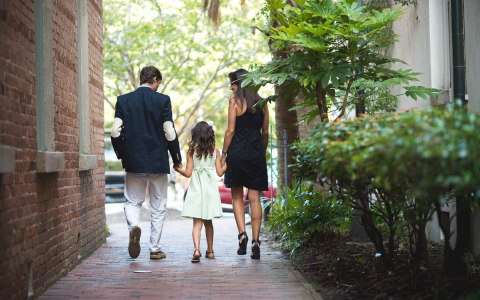 Couple with daughter walking down brick path