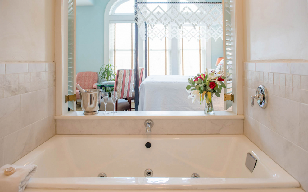 Marble bathtub with window type opening leading to bedroom