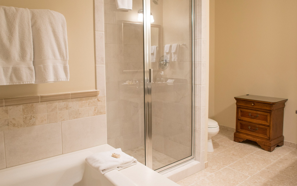 Bathroom with marble tub next to glass door shower & beige tile flooring