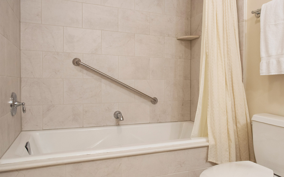 Bathtub with beige shower curtain