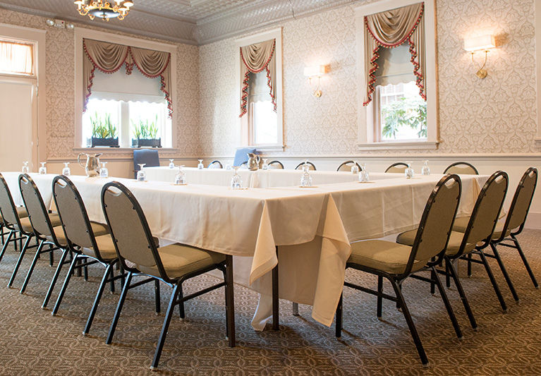 Event room with tables set in u formation with chairs