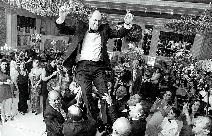 groom being lifted up on a chair on the dancefloor