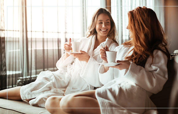 two woman in robes drinking coffee