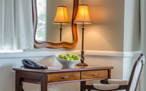 desk and chair with a phone, lamp and bowl of apples