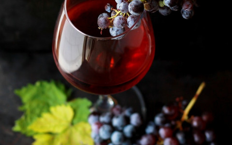 red grapes in a wine glass with red wine in it