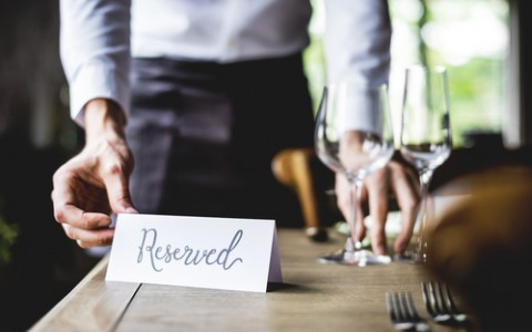 waiter placing a reserved card on dining table in restaurant