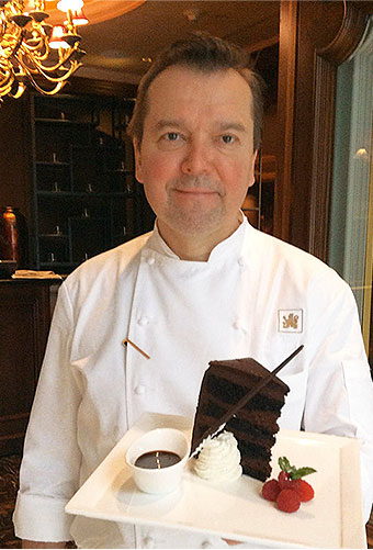 chef holding a large piece of chocolate cake