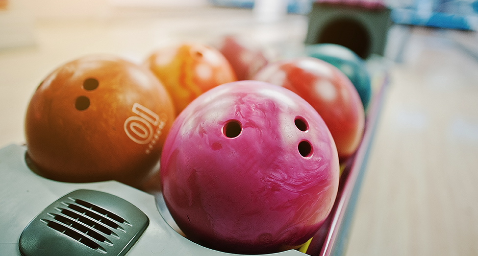 Close up of bowling balls on rack next to ally